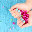 Beautiful woman hands with blue manicure holding pink beads, on color background — Stock Photo