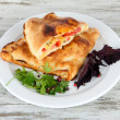 Pizza calzones on plate on wooden table — Stock Photo