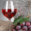 Ripe delicious grapes with glass of wine on table on gray background — Stock Photo #27544477