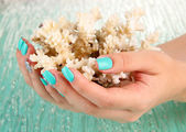 Beautiful woman hands with blue manicure holding coral, on color background — Stock Photo