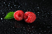 Ripe sweet raspberries with drops on dark background — Stock Photo