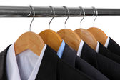 Suits with shirts on hangers on white background — Stock Photo