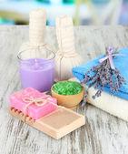 Natureza morta com vela de lavanda, sabonete, massagem bolas, garrafas, sabão e lavanda fresca, na mesa de madeira no fundo brilhante — Fotografia Stock