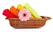 Colorful towels and flower in basket, isolated on white — Stock Photo