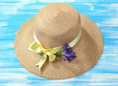 Beautiful summer hat on blue wooden background — Stock Photo