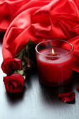 Beautiful romantic red candle with flowers and silk cloth, close up — Stock Photo