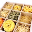 Nine types of pasta in wooden box sections close-up isolated on white — Stock Photo #27720629