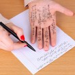 Write cheat sheet on hand on wooden table close-up — Stock Photo #27721559