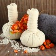 Herbal compress balls for spa treatment and towel on bamboo background — Stock Photo #27723391