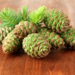 Green cones and fir tree on wooden background — Stock Photo #27726281