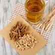 Beer in glass crunches, and nuts on napkin on wooden table — Stock Photo