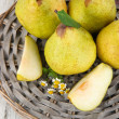 Pears on braided tray on wooden table — Stock Photo #27727397