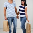 Beautiful loving couple is shopping on grey background — Stock Photo