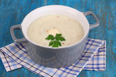 Mashed potatoes in saucepan on blue wooden table — Stock Photo