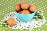 Eggs in bowl on green tablecloth close-up — Stock Photo