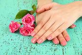 Manos de mujer con manicura rosa y flores, sobre fondo de color — Foto de Stock