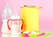Bottles with milk and food for babies on pink background — Fotografia Stock
