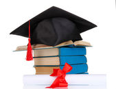 Grad hat with diploma and books isolated on white — Stock Photo