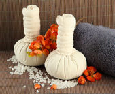 Herbal compress balls for spa treatment and towel on bamboo background — Stock Photo