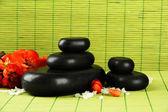 Wellness kameny a květiny na bambusové pozadí — Stock fotografie