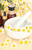 Aceites esenciales y flores de manzanilla en mortero sobre mesa de madera — Foto de Stock