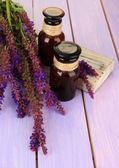 Medizin-flaschen und salvia blumen auf lila hölzernen hintergrund — Stockfoto