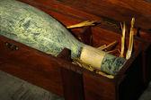 Antigua botella de vino en caja de madera, sobre fondo marrón oscuro — Foto de Stock