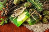 Handgemachte seife und grünen tannenzapfen auf holztisch — Stockfoto