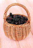 Ripe mulberries in wicker basket on wooden background — Stockfoto