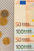 Euro banknotes and euro cents on grey background — Photo