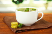 Cup of soup with bouillon cubes on wooden table — Foto Stock