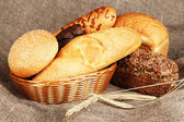 Baked bread in wicker basket on burlap background — Stock Photo