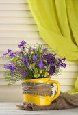 Beautiful bouquet of wildflowers in cup on wooden table — Stock Photo