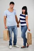 Hermosa pareja amorosa es ir de compras en fondo gris — Foto de Stock