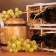 Wooden case with wine bottle, barrel, wineglass and grape on wooden table on brown background — Stock Photo #27732213