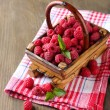 Ripe sweet raspberries in basket on wooden background — Stock Photo