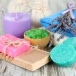 Still life with lavender candle, soap, massage balls, bottles,  soap and fresh lavender, on wooden background — Stock Photo