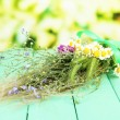 Bouquet of wild flowers and herbs, on wooden table on bright background — Stock Photo