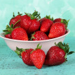 Strawberries in plate on blue background — Stock Photo #27734565