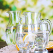 Stock Photo: Glass pitchers of water and glasses on wooden table on natural background