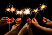 Beautiful sparklers in hands on black backgroun — Stock Photo