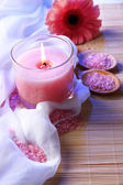 Beautiful candle with flower on white cloth, close up — Stock Photo
