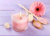 Beautiful pink candle with flower on purple wooden background — Stock Photo