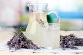 Lavender lemonade in glass jug, on napkin, on bright background — Stock Photo