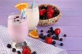 Delicious milk shakes with orange and blackberry on wooden table close-up — Stock Photo