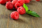 Ripe sweet raspberries on wooden background — Stock Photo