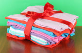 Pile of clothing with red ribbon and bow on table on green background — Stock Photo