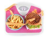 Hot-dog, hamburger and fries on scales isolated on white — Stock Photo