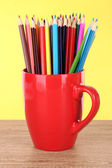 Colorful pencils in cup on table on yellow background — Stock Photo