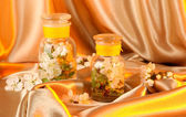 Flowering branches in glass banks on beige fabric background — Stock Photo